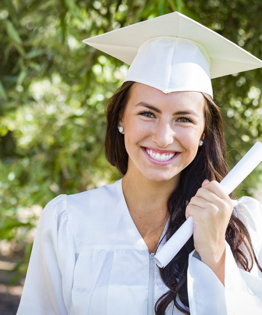 Attractive Mixed Race Girl Celebrating Graduation Outside In Cap and Gown with Diploma in Hand.